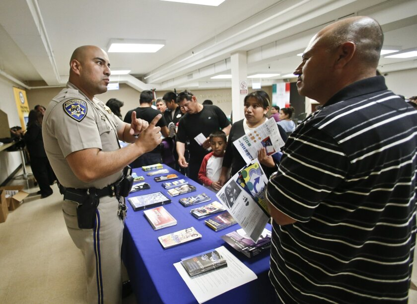 FILE - In this file photo taken on Wednesday, April 23, 2014, California Highway Patrol officer Armando Garcia explains to immigrants the process of getting a drivers license during an information session at the Mexican Consulate, in San Diego. California is gearing up to start issuing driver's lic