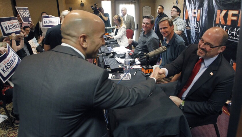 California Republican gubernatorial candidates Neel Kashkari, left, and Tim Donnelly shake hands at a radio debate in Anaheim earlier this month. A new Stanford University poll shows Donnelly leading his GOP rival in the bid to challenge Democratic Gov. Jerry Brown in November.