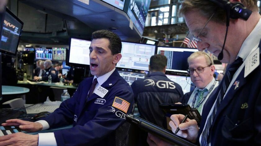 Specialist Peter Mazza, left, works with traders on the floor of the New York Stock Exchange, Wednes