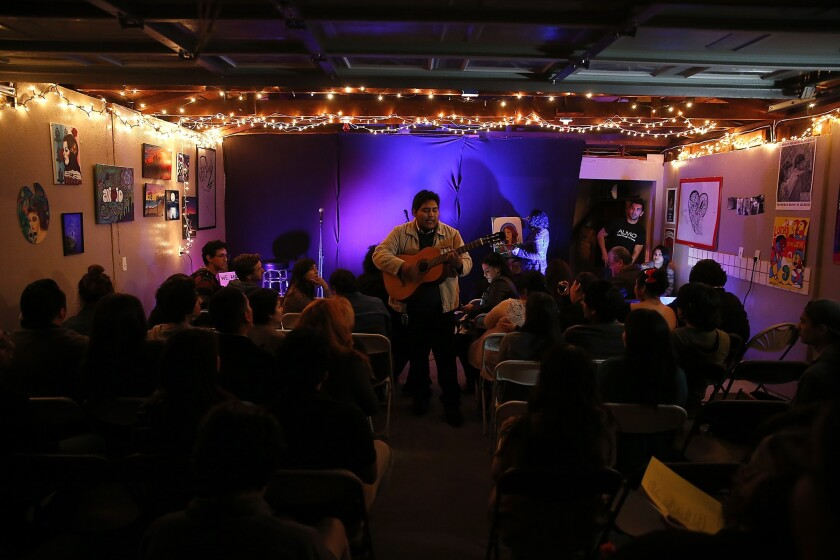 """Dozens of people crowd Eric Contreras' parents' garage in Bell as Julio Marquez performs folk songs at an open-mic night called Alivio, Spanish for """"relief."""""""