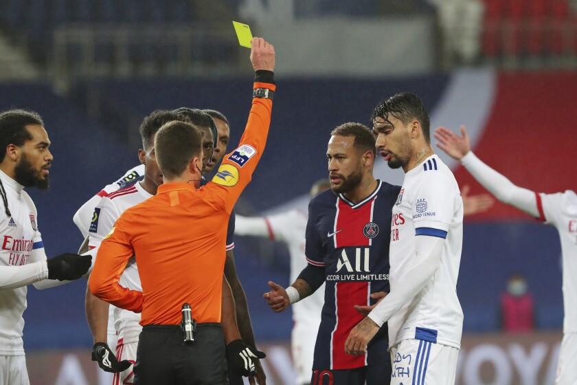 Referee Benoit Bastien shows a yellow card to PSG's Neymar, center, during the League One soccer match between Paris Saint Germain and Lyon, at the Parc des Princes stadium in Paris, France, Sunday, Dec. 13, 2020. (AP Photo/Thibault Camus)
