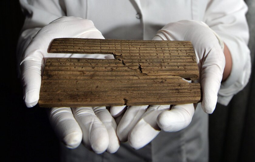 Luisa Duarte, a conservator for the Museum of London, holds a piece of wood with the Roman alphabet written on it in, in London, Wednesday, June 1, 2016. Archaeologists say they have discovered the oldest handwritten document ever found in Britain among hundreds of 2,000-year-old waxed tablets from