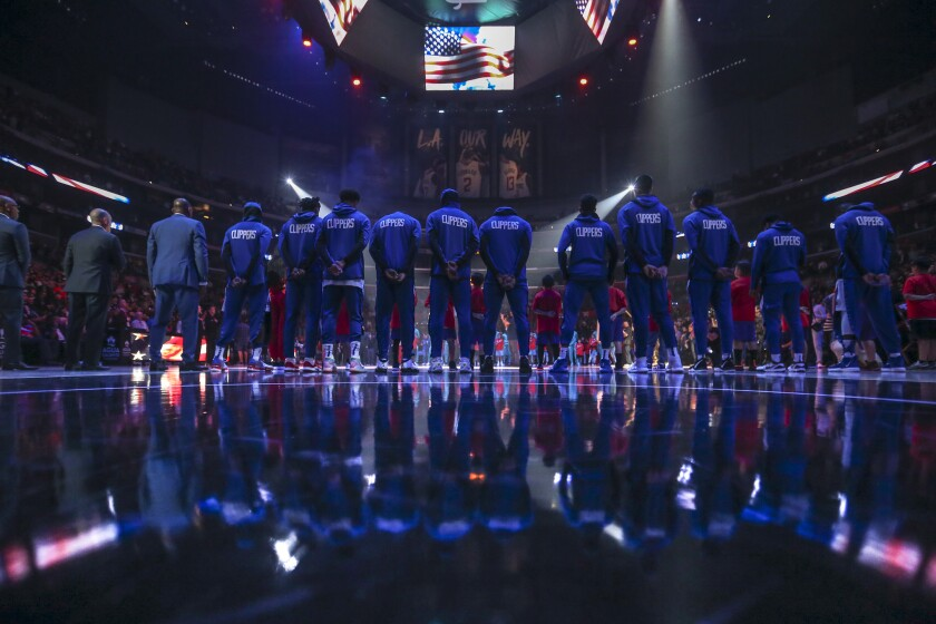 The Clippers and the Charlotte Hornets stand during the national anthem prior to the Clippers' 111-96 win at Staples Center on Monday.