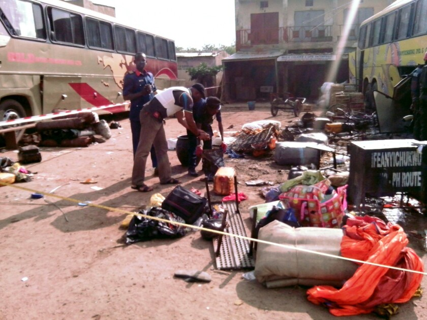 Security officers examine abandoned items at the scene of a blast in the northern Nigerian city of Kano on July 24. The city has recently been the site of several suicide bombings involving young women.