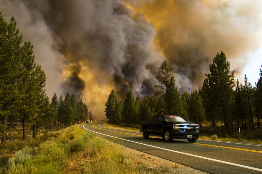 A truck drives down a road lined with trees as smoke and fire burn in the background