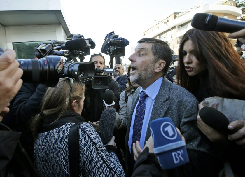 Massimo Carminati lawyer Bruno Naso is chased by reporters as he arrives at a court in Rome, Thursday, Nov. 5, 2015. More than 40 people are under trial and charged of being part of a mafia style corruption system aimed at winning public contracts for the management of garbage collection, refugees