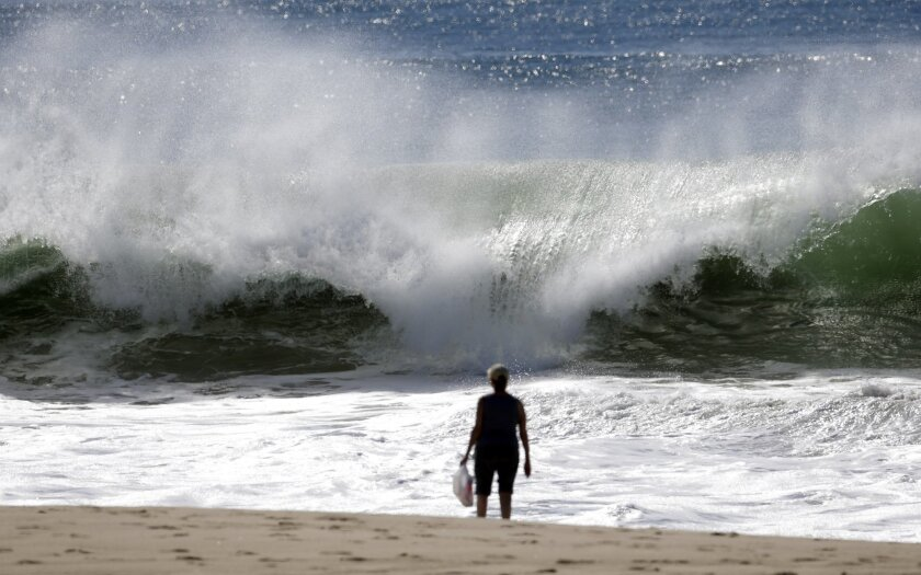 A woman watches the high surf building on the west-facing coast in El Segundo, Calif., on Wednesday, Feb. 24, 2016. Surf is building along much of the California coast and beachgoers are warned of dangerous waves, rip currents and possibly some minor flooding. The National Weather Service has issued a high surf advisories Wednesday. Waves could reach 20 feet north and south of San Francisco, 18 feet along the Central Coast while sets topping 12 feet are expected from Los Angeles to San Diego. (AP Photo/Nick Ut)