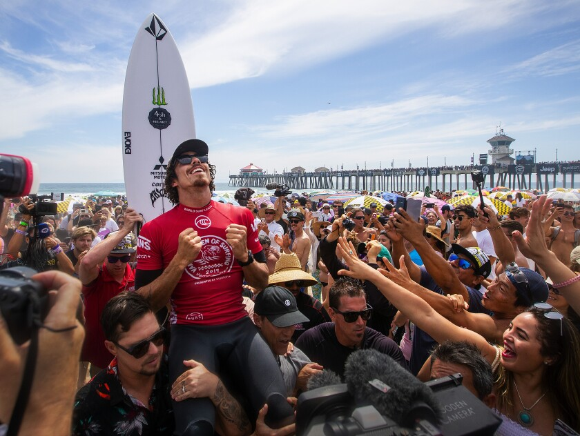 Yago Dora of Brazil celebrates with fans in Huntington Beach after winning the 2019 Vans U.S. Open of Surfing.