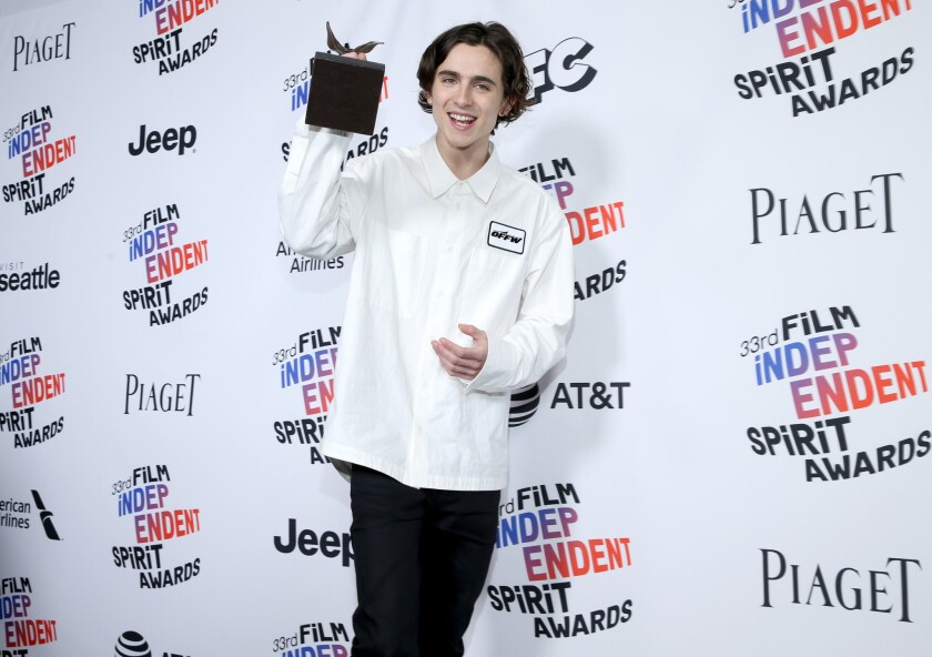 """Timothée Chalamet poses with his best male lead statue at the Independent Spirit Awards in Santa Monica on Saturday. The """"Call Me By Your Name"""" star wore an Off White c/o Virgil Abloh white utility shirt."""