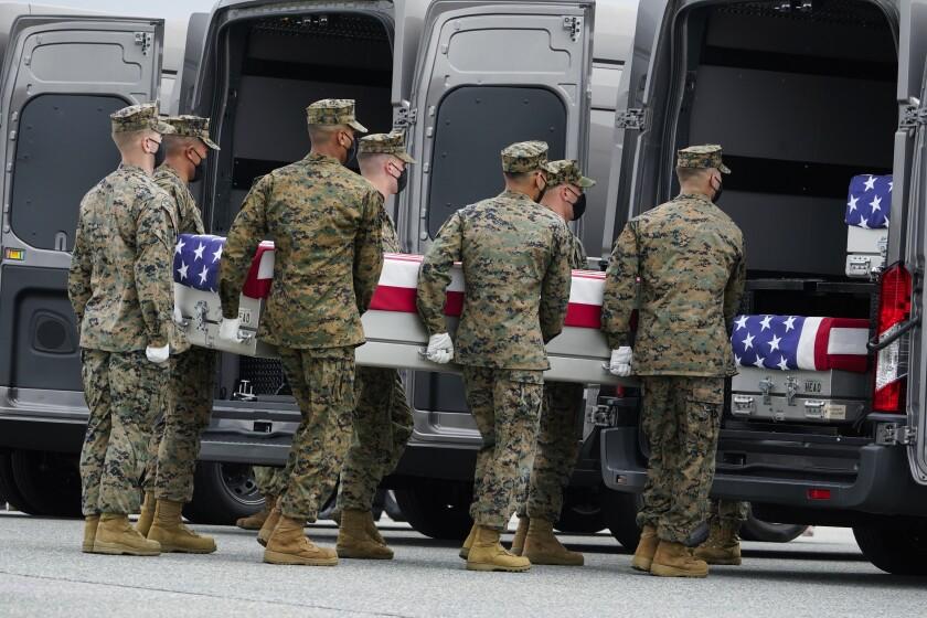 جسد یک تفنگدار دریایی به یک وسیله نقلیه منتقل می شود.