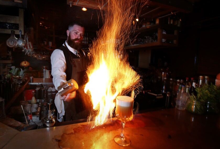 """Andrew Winters, bartender at the Blind Rabbit speakeasy was concocting the """"Wait for it"""" a flaming drink, at the Anaheim Packing House in Anaheim."""