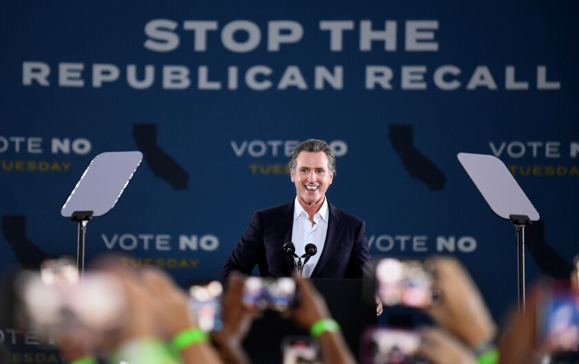 """California Gov. Gavin Newsom smiles onstage at a rally against a backdrop reading """"Stop the Republican recall"""""""
