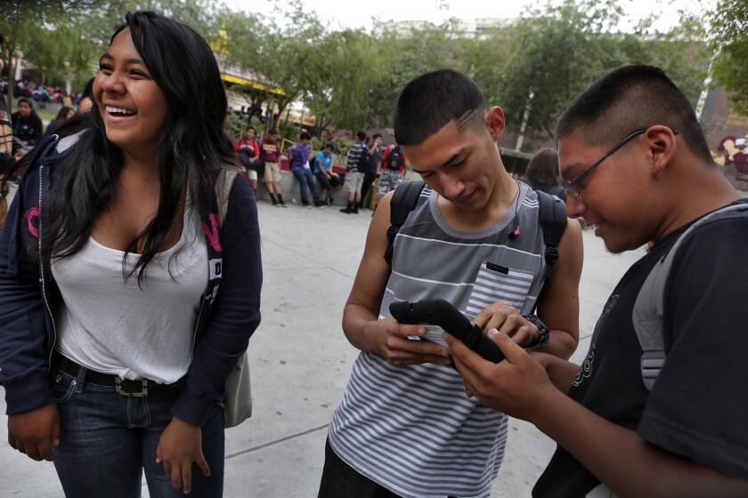 Bianca Gomez, left, Humberto Salazar and Doroteo Cruz are happy to receive iPads at Theodore Roosevelt High School, as part of the first phase of L.A. Unified's iPad rollout.