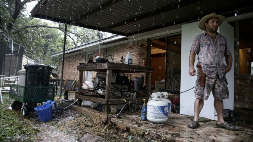 Wyatt Sebesta, 34, carries a revolver as he finishes moving most of the contents of his home to high