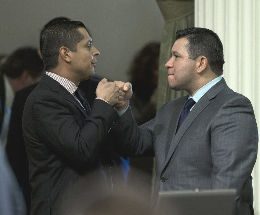 Assemblyman Eduardo Garcia, D-Coachella, right, receives congratulations from Assemblyman Miguel Santiago, D-Los Angeles, after his measure to give lawmakers more oversight over the state's efforts to combat global warming was approved by the Assembly Wednesday, Aug. 24, 2016, in Sacramento, Calif. Garcia's bill, AB197, would add two legislators as non-voting members of the Air Resources Board, which enforces California's law targeting green-house gas reductions. (AP Photo/Rich Pedroncelli)