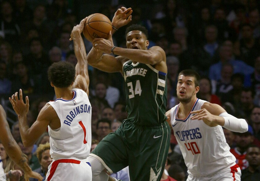 Bucks forward Giannis Antetokounmpo looks to pass out of the defense of Clippers guard Jerome Robinson and center Ivica Zubac.