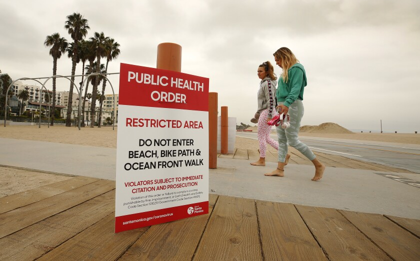 Kim Abt, left, and Rachel Portugal walk the beach after a social media workout Tuesday morning in Santa Monica.