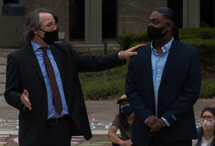 Assistant Public Defender Scott Sanders, left, and Mohamed Sayem stand outside the courthouse.