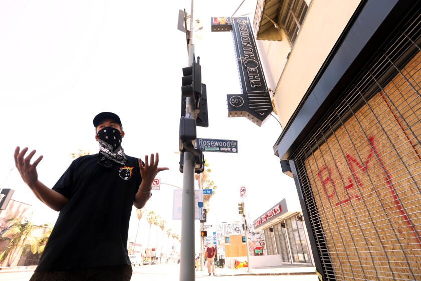 Bobby Kim, co-owner of the Hundreds store, stands in front of the boarded-up establishment on June 3, 2020.