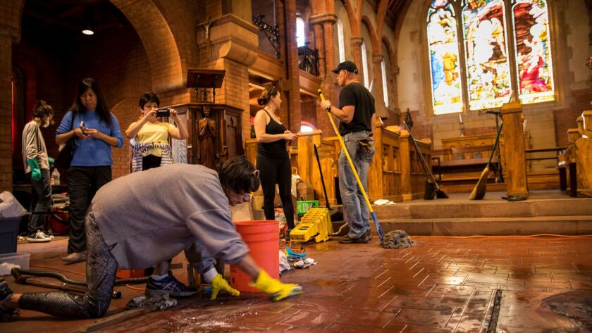 Volunteers clean up damage caused by a small fire inside of Church of the Angels in Pasadena.