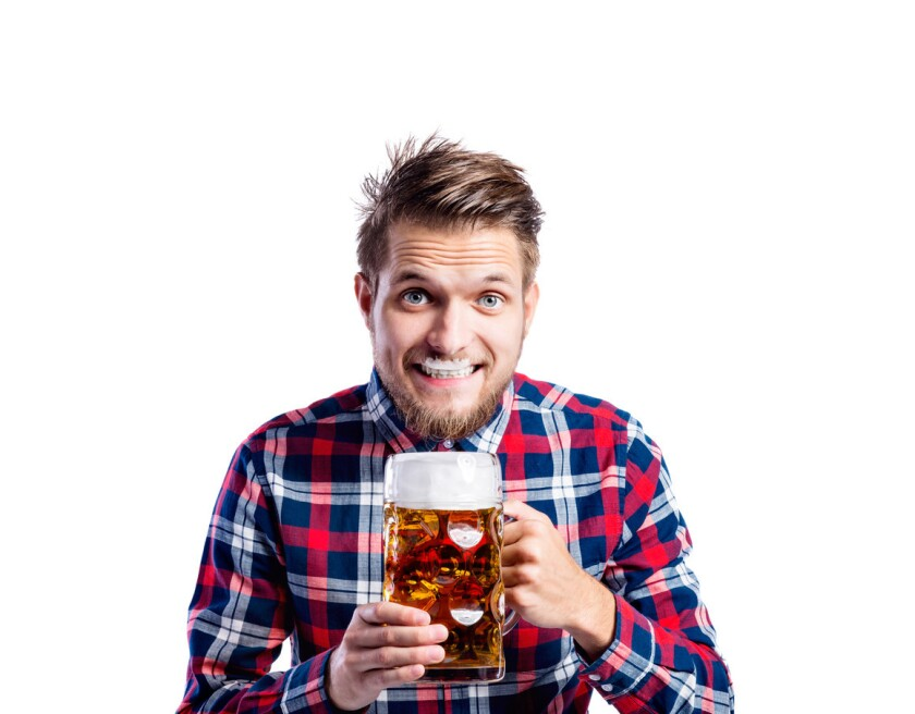 Hipster man in checked shirt drinking beer, studio shot