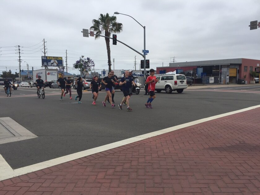 A group of runners participating in Law Enforcement Torch Run for Special Olympics passes through Barrio Logan in San Diego