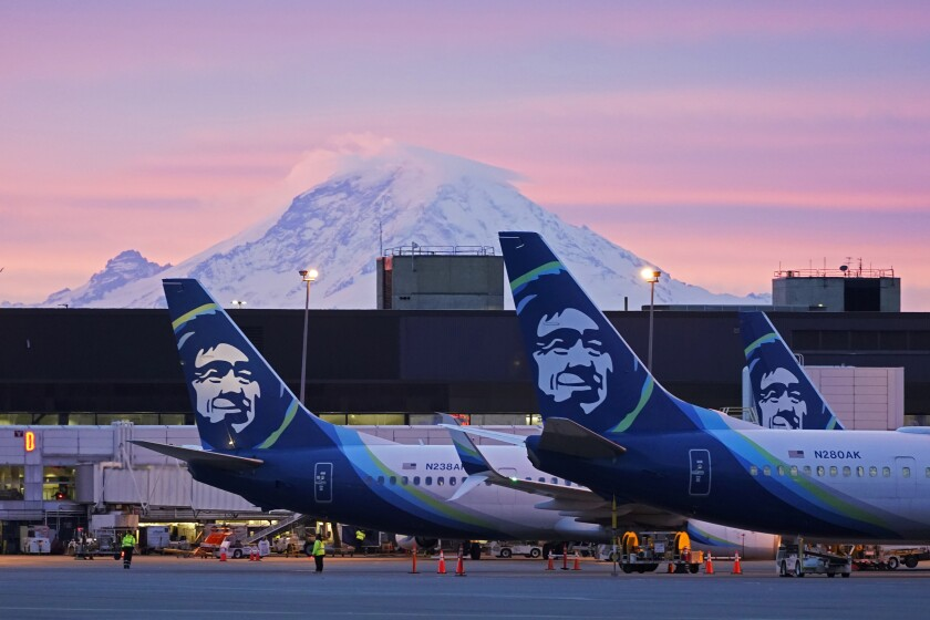 FILE — In this March 1, 2021 file photo Alaska Airlines planes are shown parked at gates with Mount Rainier in the background at sunrise, at Seattle-Tacoma International Airport in Seattle. Alaska Air Group has told its 22,000 employees they will be required to get a COVID-19 vaccination. There are some exceptions to the policy, which has shifted since last month, the The Seattle Times reported. In an email Thursday evening to all Alaska Airlines and Horizon Air employees, the Seattle-based company said employees will now be required to be fully vaccinated or approved for a reasonable accommodation. (AP Photo/Ted S. Warren,File)