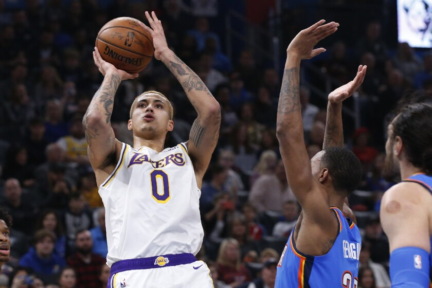 Los Angeles Lakers forward Kyle Kuzma (0) shoots in front of Oklahoma City Thunder guard Terrance Ferguson, center, in the first half of an NBA basketball game Saturday, Jan. 11, 2020, in Oklahoma City. (AP Photo/Sue Ogrocki)