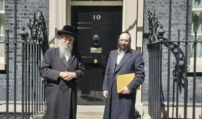 In this photo provided by Chaya Spitz, Rabbi Avrohom Pinter, left, stands beside Joel Friedman, right, the director of Public Affairs for the Interlink Foundation, an umbrella organization for Orthodox Jewish charities on July 4, 2019 in Downing Street, London. Pinter gave his life to save his neighbors. When the British government ordered a lockdown to slow the spread of coronavirus, Pinter went door-to-door to deliver the public health warning to the ultra-Orthodox Jews in northeast London. Within days, the 71-year-old rabbi had caught the disease and died. (Chaya Spitz via AP)