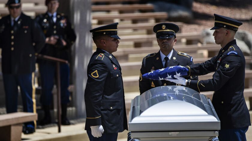 Honor guard members fold the American flag to give to family members of U.S. Army Staff Sgt. David Rosenkrantz, who was killed during World War II but whose remains were not identified until this year.