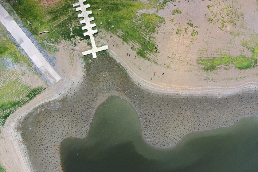 This June 19, 2015 aerial photo shows a boat ramp and dock rising high above the waterline of La Plata reservoir in Toa Alta, Puerto Rico. Puerto Rico expanded water rationing across several municipalities as it continues to confront a drought of potentially historic proportions. More than 200,000