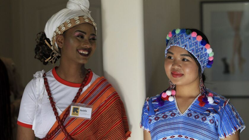 Nesteha Hassen, 17, of Ethiopia, left, and Ywahay Moo, 16, of Thailand, are dressed in a native costume waiting to walk the runway at a fashion show Sunday in Leucadia featuring young women who are recent refugees to the U.S. photo by Bill Wechter