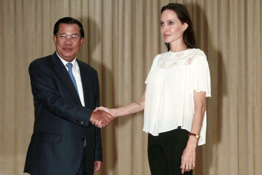 "FILE - In this Sept. 17, 2015, file photo, U.S. actress Angelina Jolie Pitt poses for a photo with Cambodian Prime Minister Hun Sen in Phnom Penh, Cambodia. Angelina Jolie Pitt first came to Cambodia 16 years ago to film ""Lara Croft: Tomb Raider"" - the gun-toting, bungee-jumping, supremely toned ac"