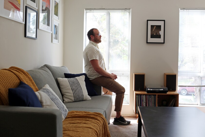 A man sits on the arm of a living-room couch.