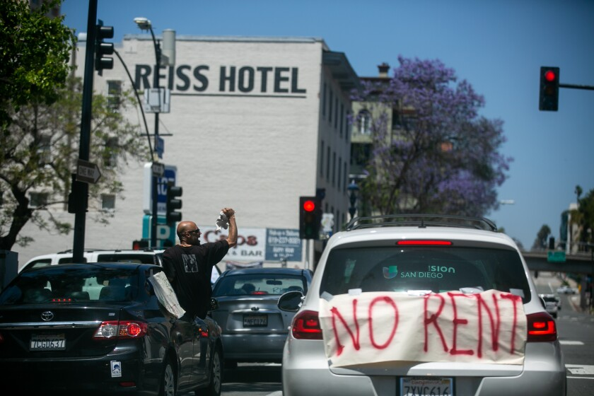"""Protesters pass through downtown San Diego demonstrating from their cars as part of a """"Food Not Rent"""" caravan"""
