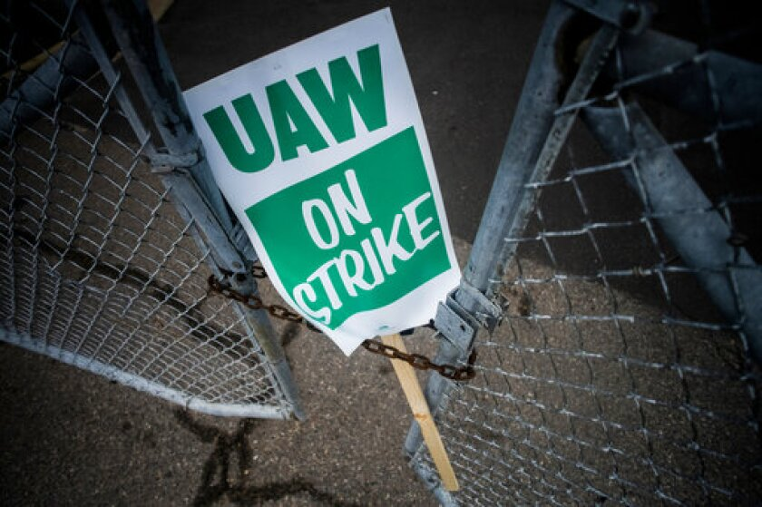 FILE - In this Monday, Sept. 16, 2019, file photo, a United Auto Workers strike sign rests between the chains of a locked gate entrance outside of Flint Engine Operations in Flint, Mich. As the United Auto Workers' strike against General Motors continues, consumers, the company and striking workers are starting to get pinched. (Jake May/The Flint Journal via AP, File)