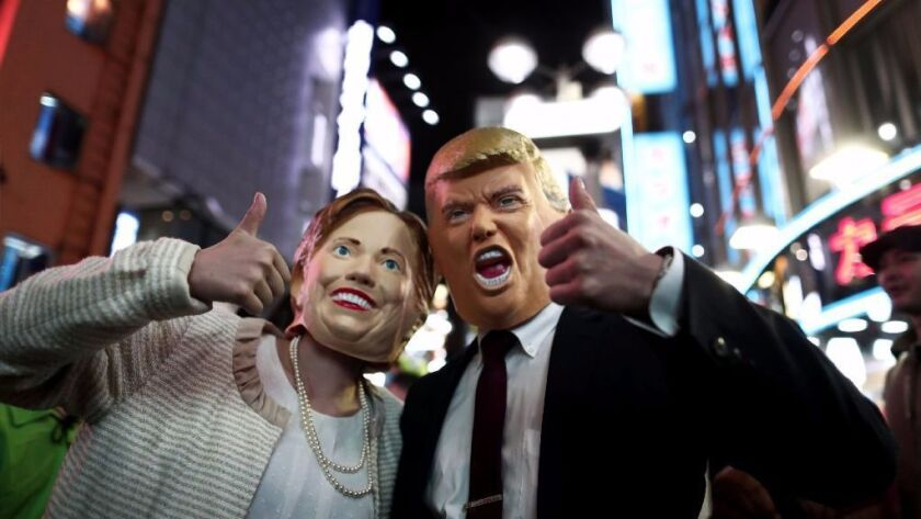 People wear costumes of US presidential candidates, Hillary Clinton (L) and Donald Trump (R) as they take part in a Halloween parade in Tokyo on October 29, 2016.
