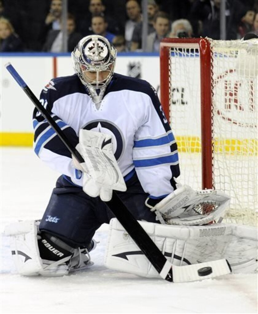 Winnipeg Jets goaltender Ondrej Pavalec deflects the puck during the second period of an NHL hockey game against the New York Rangers on Monday, April 1, 2013, at Madison Square Garden in New York. (AP Photo/Bill Kostroun)