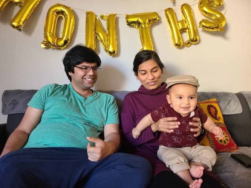 Swati Tyagi sits with her husband, Ashim Rai, and 11-month-old son, Miransh.