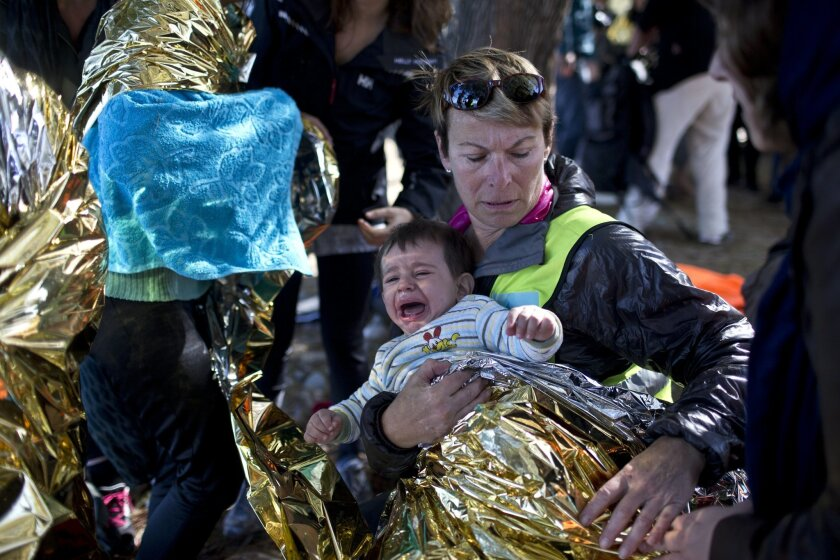 A volunteer wraps a baby in an emergency blanket for warmth as people disembark from a rubber boat from neighboring Turkey at a beach on the northern shore of Lesbos, Greece, Monday, Nov. 2, 2015. More than 300,000 people have traveled on dinghies and boats from nearby Turkey to Lesbos this year, w