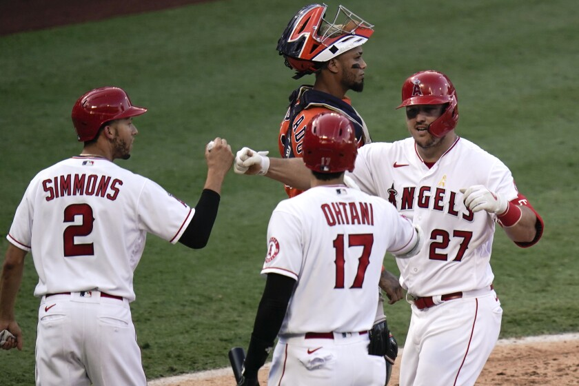 Los Angeles Angels' Mike Trout, right, celebrates his two-run home run with Andrelton Simmons, left, and Shohei Ohtani, of Japan, during the third inning of the first baseball game of a doubleheader against the Houston Astros, Saturday, Sept. 5, 2020, in Anaheim, Calif. (AP Photo/Jae C. Hong)