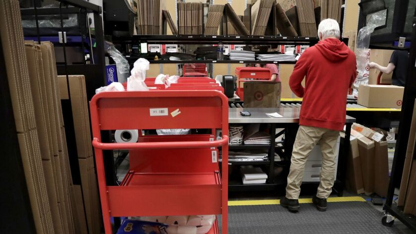 FILE- In this Nov. 16, 2018, photo an assembly line worker packages items from an online order to be