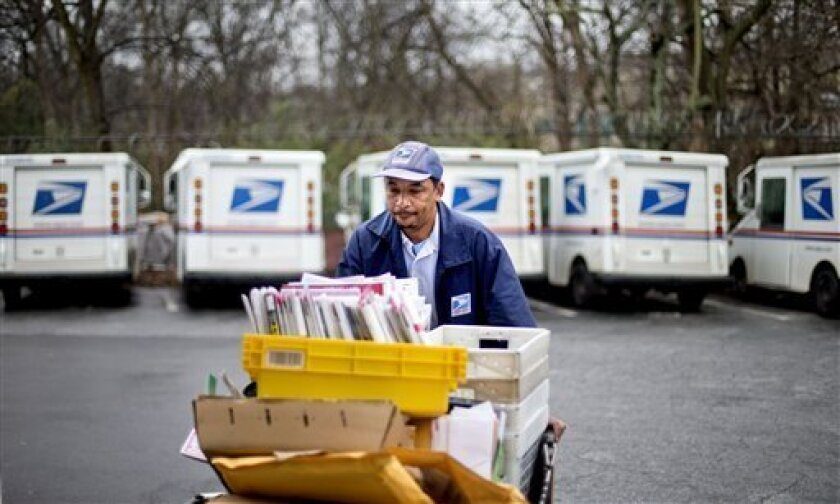 FILE - In this Feb. 7, 2013 file photo, U.S. Postal Service letter carrier Michael McDonald gathers mail to load into his truck before making his delivery run in the East Atlanta neighborhood, in Atlanta. The U.S. Postal Service says it will delay plans to cut Saturday mail delivery because Congres