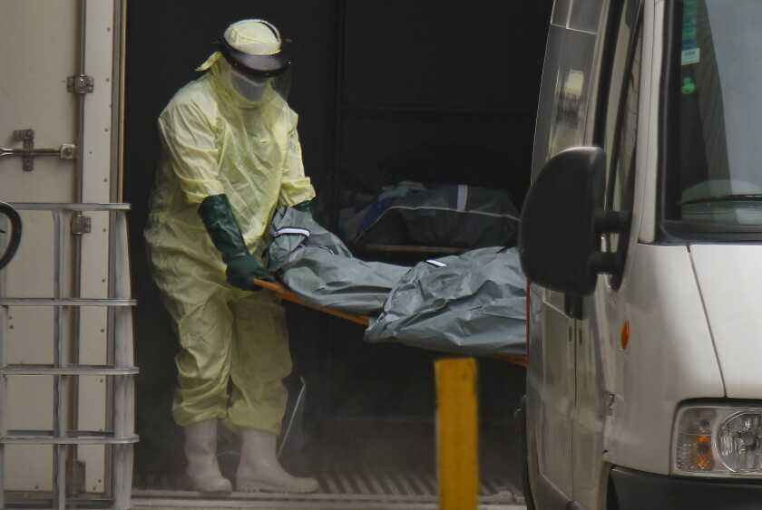 Health workers remove the body of a COVID-19 victim from a container, being used as a makeshift morgue, to turn over to a family outside the Joao Lucio public Hospital in Manaus, Amazonas state, Brazil, Monday, Jan. 4, 2021. (AP Photo/Edmar Barros)