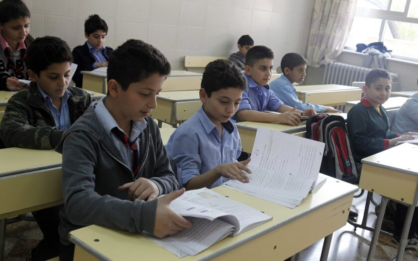 Syrian students attend a class in the Yuhana al-Dimashqi School the day after mortar shells hit the school, in Bab Sharqi neighborhood, Damascus, Syria, November 12, 2013.