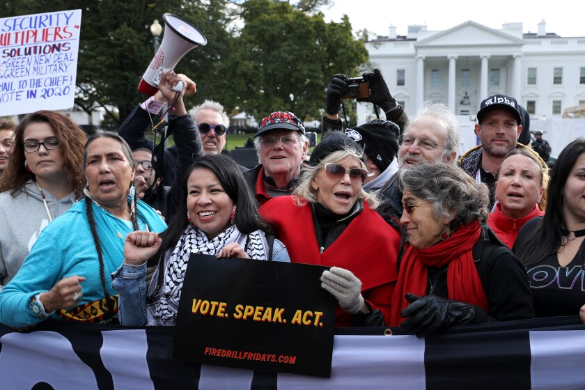 """Actor Jane Fonda, at center in bright red coat, rallies with dozens of others in front of the White House in November as part of her """"Fire Drill Fridays"""" protesting climate change."""