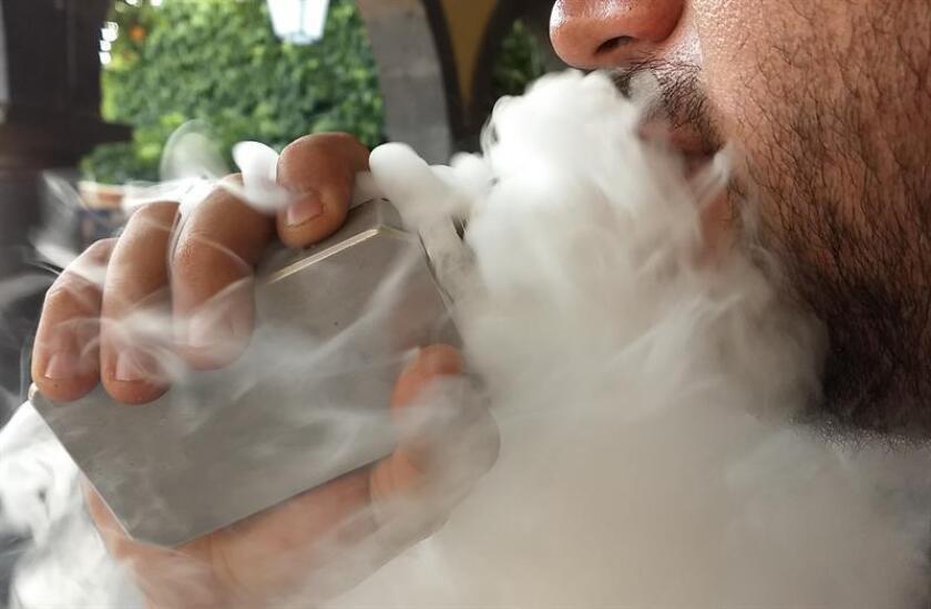 Fotografía del 13 de enero de 2018, de Martín Alonso, de 31 años, fumando un cigarrillo electrónico en una calle de la ciudad de Guadalajara (México). EFE