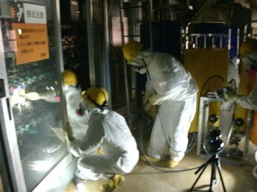 In this photo taken on June 22, 2011 and released on Thursday, June 23, 2011 by Tokyo Electric Power Co. (TEPCO), workers in protective suits set up temporary pressure gauges in the Unit 2 reactor building at the tsunami-damaged Fukushima Dai-ichi nuclear plant in Okuma, Fukushima prefecture, northern Japan. (AP Photo/Tokyo Electric Power Co.)