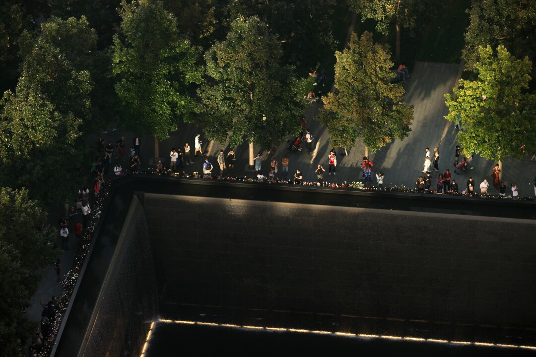 Light bounces off of nearby buildings to light the edge of the north pool at the National September 11 Memorial & Museum.