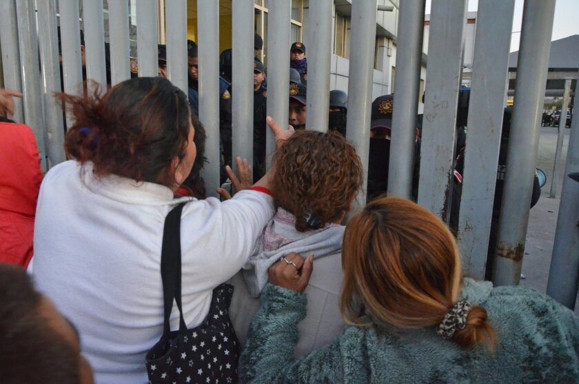 Relatives of inmates stand outside the Topo Chico prison facing police, after a riot broke out around midnight, in Monterrey, Mexico, Thursday, Feb. 11, 2016. Dozens of inmates were killed and several injured in a brutal fight between two rival factions at a prison in northern Mexico on Thursday, t